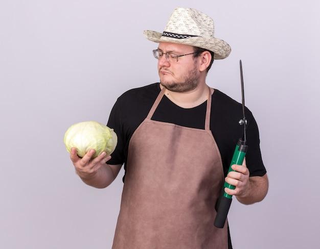 Pensando giovane giardiniere maschio che indossa il cappello da giardinaggio tenendo i clippers guardando il cavolo in mano isolato sul muro bianco