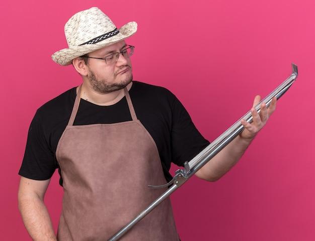 Pensando giovane giardiniere maschio che indossa cappello da giardinaggio tenendo e guardando il rastrello di foglia isolato sulla parete rosa