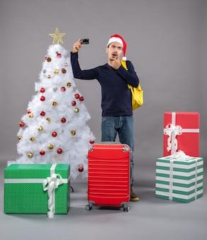 회색에 크리스마스 트리 근처 카드 서를 들고 생각 젊은 남자