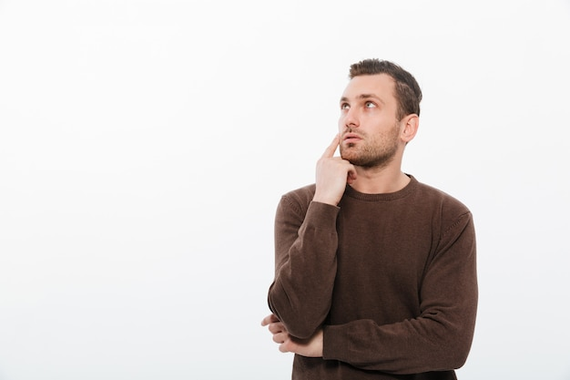Thinking young man standing isolated