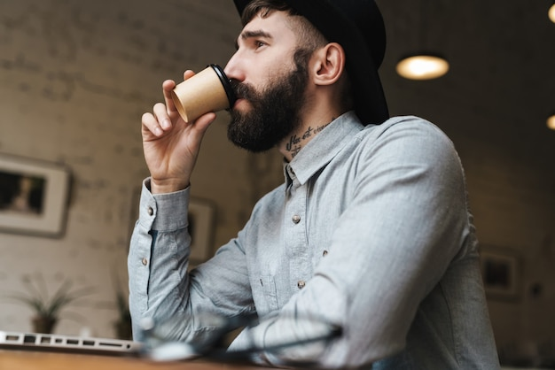 Thinking young man wearing hat using laptop and drinking coffee while sitting at table in cafe indoors