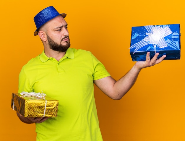Thinking young man wearing party hat holding and looking at gift boxes isolated on orange wall