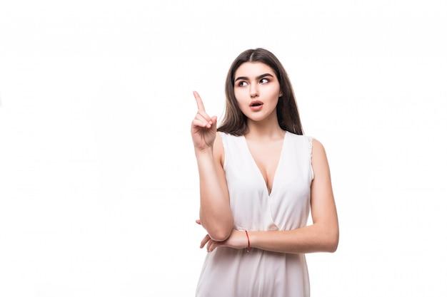 Думающая молодая модель в современном белом платье на белом
