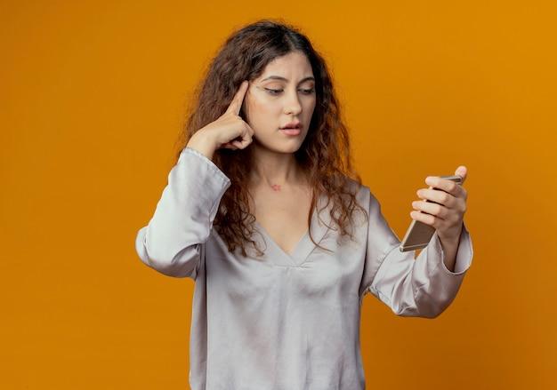 Pensando giovane bella ragazza che tiene e guardando il telefono e mettendo il dito sulla testa isolata sulla parete gialla