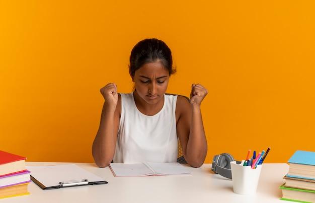 Pensando giovane studentessa seduto alla scrivania con strumenti scolastici guardando il taccuino sulla scrivania e mostrando sì gesto isolato sulla parete arancione