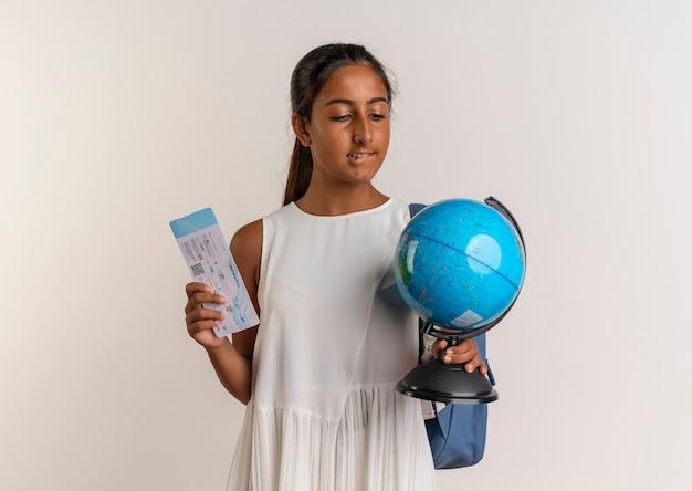 Pensando giovane studentessa che indossa la borsa posteriore che tiene il biglietto e guardando il globo in mano isolato sul muro bianco