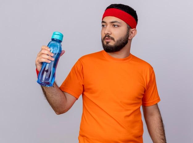 白い背景で隔離の水のボトルを保持しているヘッドバンドとリストバンドを身に着けている側を見て考えている若いスポーティな男