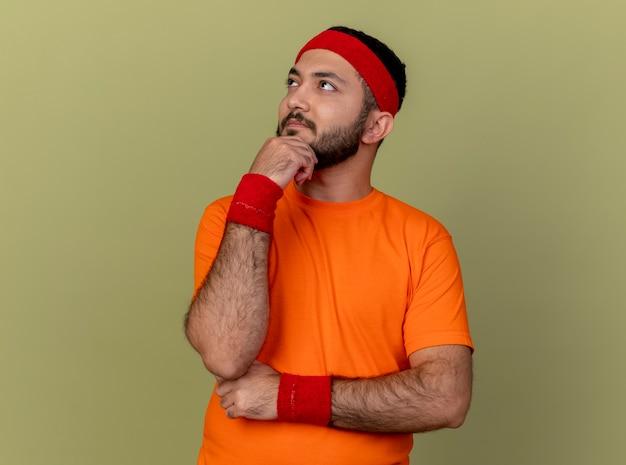 オリーブグリーンの背景で隔離のあごに手を置くヘッドバンドとリストバンドを身に着けている側を見て考えている若いスポーティな男