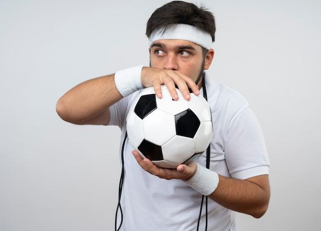 Думающий молодой спортивный человек смотрит в сторону, носит повязку на голову и браслет со скакалкой на плече, держа мяч вокруг лица, изолированного на белой стене