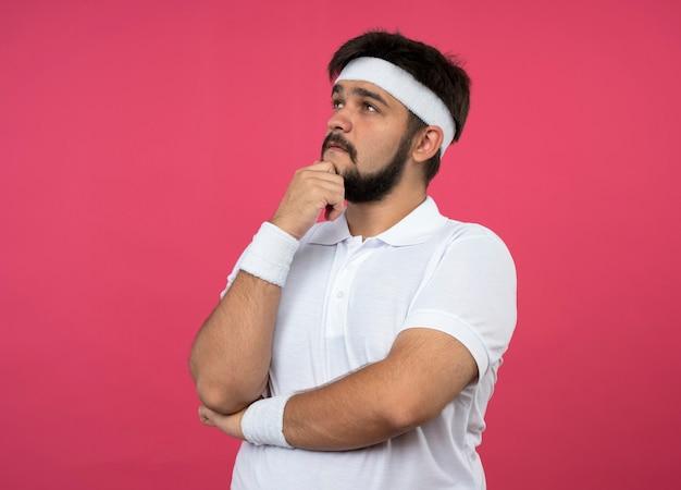 Pensando giovane uomo sportivo guardando al lato che indossa la fascia e il braccialetto ha afferrato il mento isolato sul muro rosa