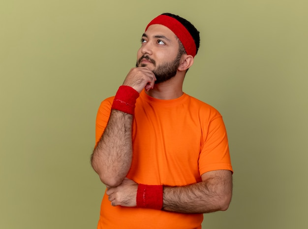 Thinking young sporty man looking at side wearing headband and wristband putting hand on chin isolated on olive green background