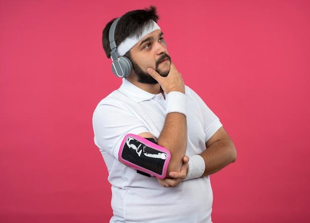 Pensando che il giovane sportivo che indossa la fascia e il braccialetto con le cuffie e la fascia da braccio del telefono ha afferrato il mento