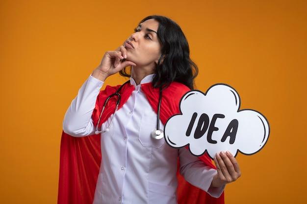 Думающая молодая девушка-супергерой смотрит в сторону в медицинском халате со стетоскопом, держа пузырь идеи, положив руку на щеку, изолированную на оранжевой стене