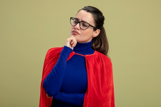 Thinking young superhero girl looking at side wearing glasses putting hand on chin isolated on olive green background