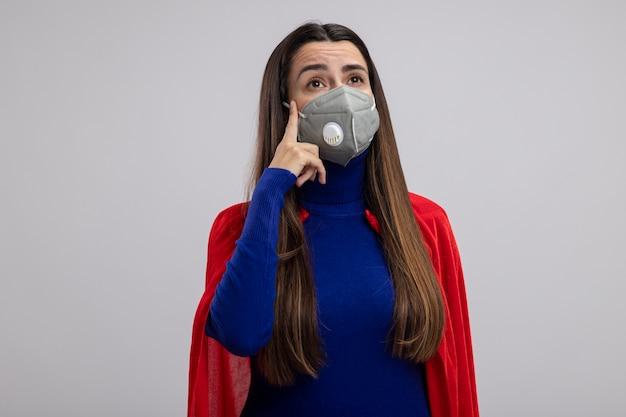 Pensando giovane ragazza del supereroe guardando al lato che indossa la mascherina medica mettendo il dito sul tempio isolato su sfondo bianco