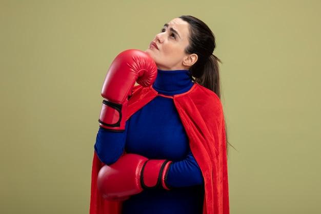 Думающая молодая девушка супергероя смотрит вверх в боксерских перчатках, положив руку под подбородок, изолированную на оливково-зеленом фоне