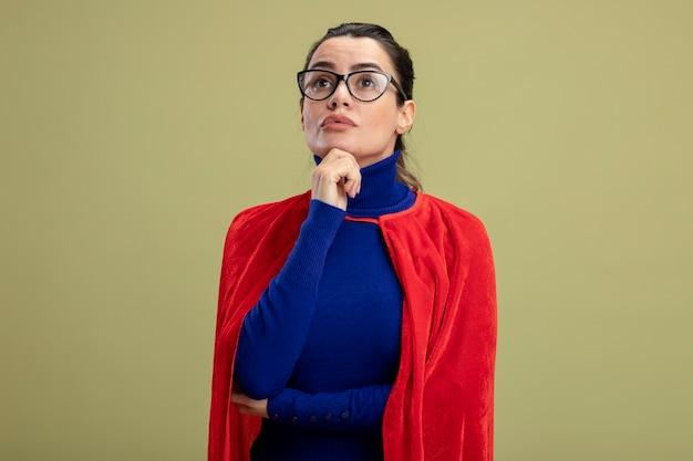 Думающая молодая девушка супергероя смотрит вверх в очках, положив руку на подбородок, изолированную на оливково-зеленом фоне