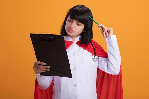 Думающая молодая девушка супергероя в стетоскопе с медицинским халатом и плащом держит и смотрит в буфер обмена, почесывая голову карандашом