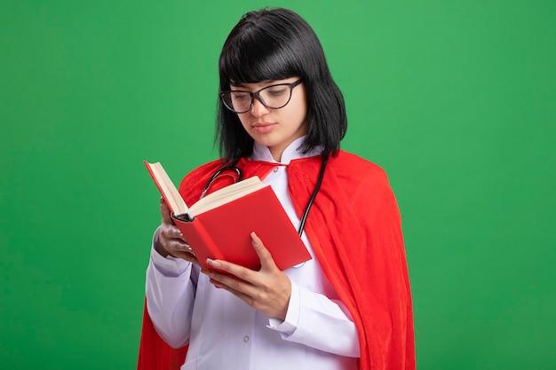 Думающая молодая девушка-супергерой в стетоскопе с медицинским халатом и плащом в очках, держащая и смотрящая на книгу, изолированную на зеленой стене