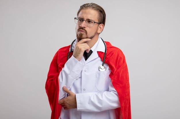 聴診器と眼鏡で医療ローブを身に着けている側を見て考えている若いスーパーヒーローの男は、白い背景で隔離のあごをつかんだ