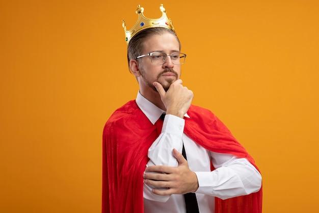 オレンジ色の背景に分離されたメガネでネクタイと王冠を身に着けている側を見て若いスーパーヒーローの男が顎をつかんだと考えています