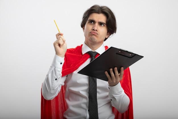クリップボードを保持し、鉛筆を上げるネクタイを身に着けている側を見て考えている若いスーパーヒーローの男