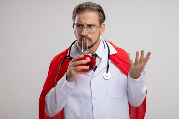 聴診器と白い背景で隔離の赤い液体で満たされた化学ガラス瓶を保持し、嗅ぐ眼鏡と医療ローブを身に着けている若いスーパーヒーローの男を考える