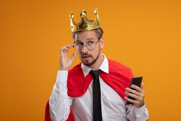 オレンジ色の背景で隔離の電話を保持している眼鏡とネクタイと王冠を身に着けている若いスーパーヒーローの男を考えて