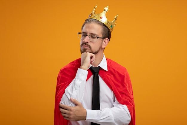 オレンジ色の背景で隔離のあごの下に手を置く眼鏡とネクタイと王冠を身に着けている若いスーパーヒーローの男を考える