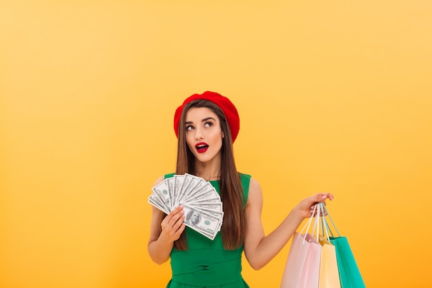 Thinking young woman holding money and shopping bags