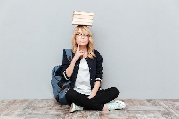 Думая студент молодой женщины держа книги на голове.