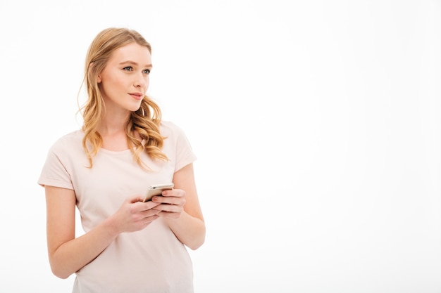 Thinking young woman using mobile phone.