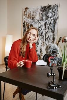 Молодая женщина-блогер держит чашку чая и думает о новом для нее контенте.