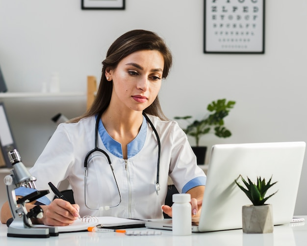 Thinkling female doctor looking on laptop