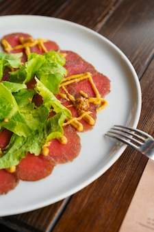 Thinly sliced beef pieces carpaccio served in a cafe