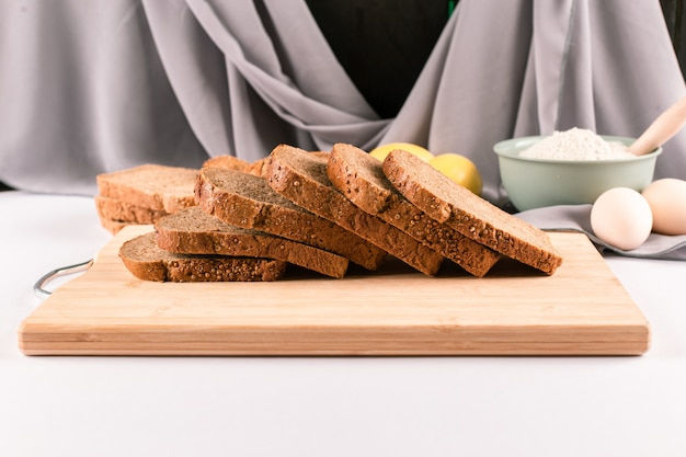 Thinly sliced dark wheat bread on a wooden board