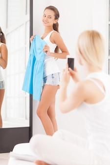 Тонкий цвет подходит вам лучше всего. красивая молодая женщина, стоящая у зеркала с синим платьем в руках и смотрящая на своего друга, сидящего на переднем плане с мобильным телефоном