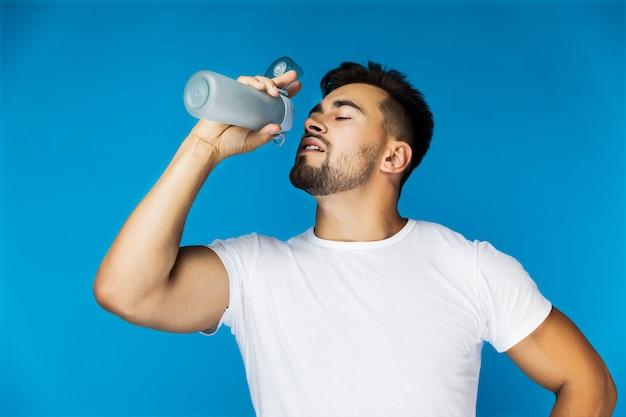 のどが渇いてハンサムな男はスポーツボトルから飲んでいます。