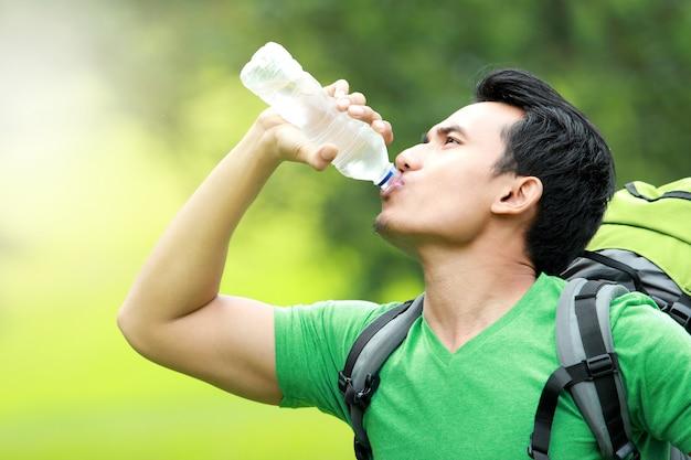 水のボトルを飲んでのどが渇いて男