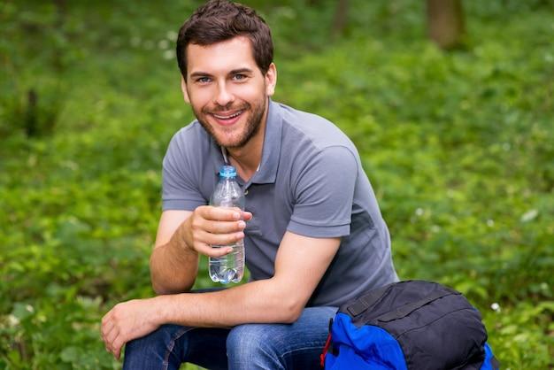 Жаждущий путник. счастливый молодой человек, держащий бутылку с водой, сидя в лесу с рюкзаком, лежащим рядом с ним с
