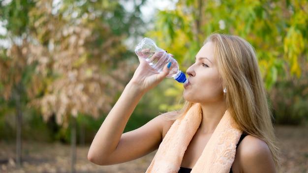 Жаждущая женщина-спортсмен пьет чистую воду в бутылках с полотенцем на шее, стоя в парке
