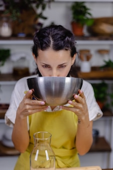 台所で金属製のボウルからアーモンドミルクを飲む喉が渇いた女性