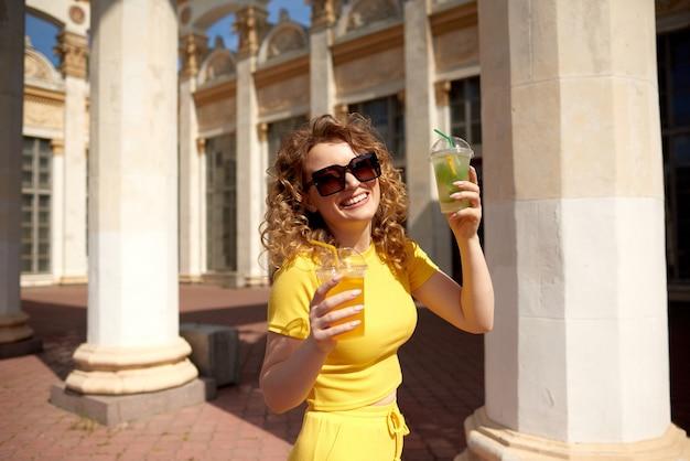 Жаждущая женщина держит в руках два стакана с апельсиновым и зеленым лимонадом в солнечный летний день