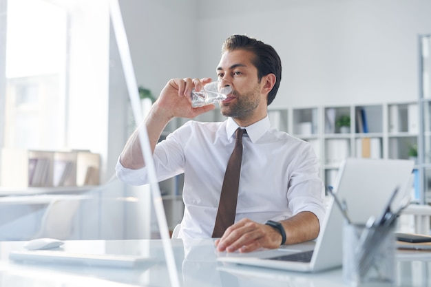 Thirsty young broker having glass of water while sitting in front of computer monitor in office