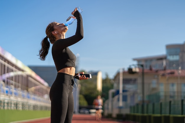 Жаждущая молодая здоровая женщина пьет воду из пластиковой бутылки