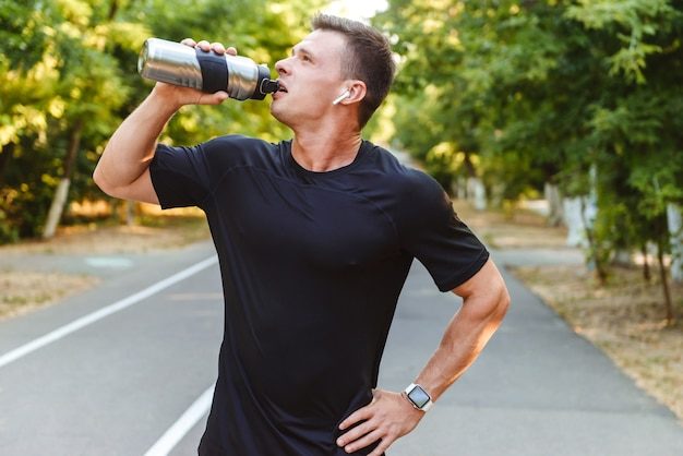 Thirsty young sportsman in earphones drinking water