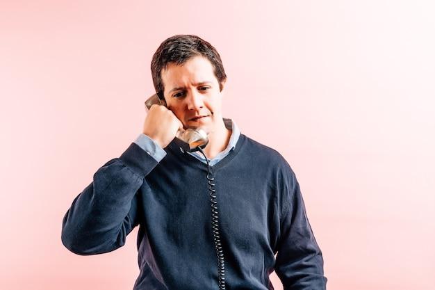 Тридцатипятилетний молодой взрослый мужчина в синей рубашке с v-образным вырезом и свитере на розовом фоне разговаривает по проводному телефону