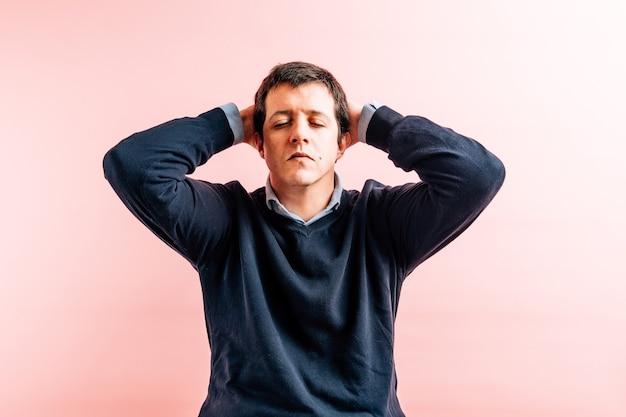 Тридцатипятилетний молодой взрослый мужчина в рубашке и синем свитере с v-образным вырезом на розовом фоне с руками на голове от боли или стресса