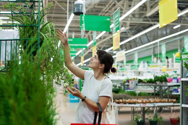 鉢植えの屋内花を持つ部門の近くのスーパーマーケットの30歳の女性