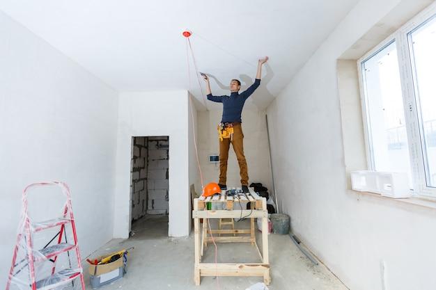 Тридцатилетний рабочий с инструментами для штукатурки стен внутри дома. штукатур выполняет ремонт внутренних стен и потолков с помощью штукатурки и штукатурки.